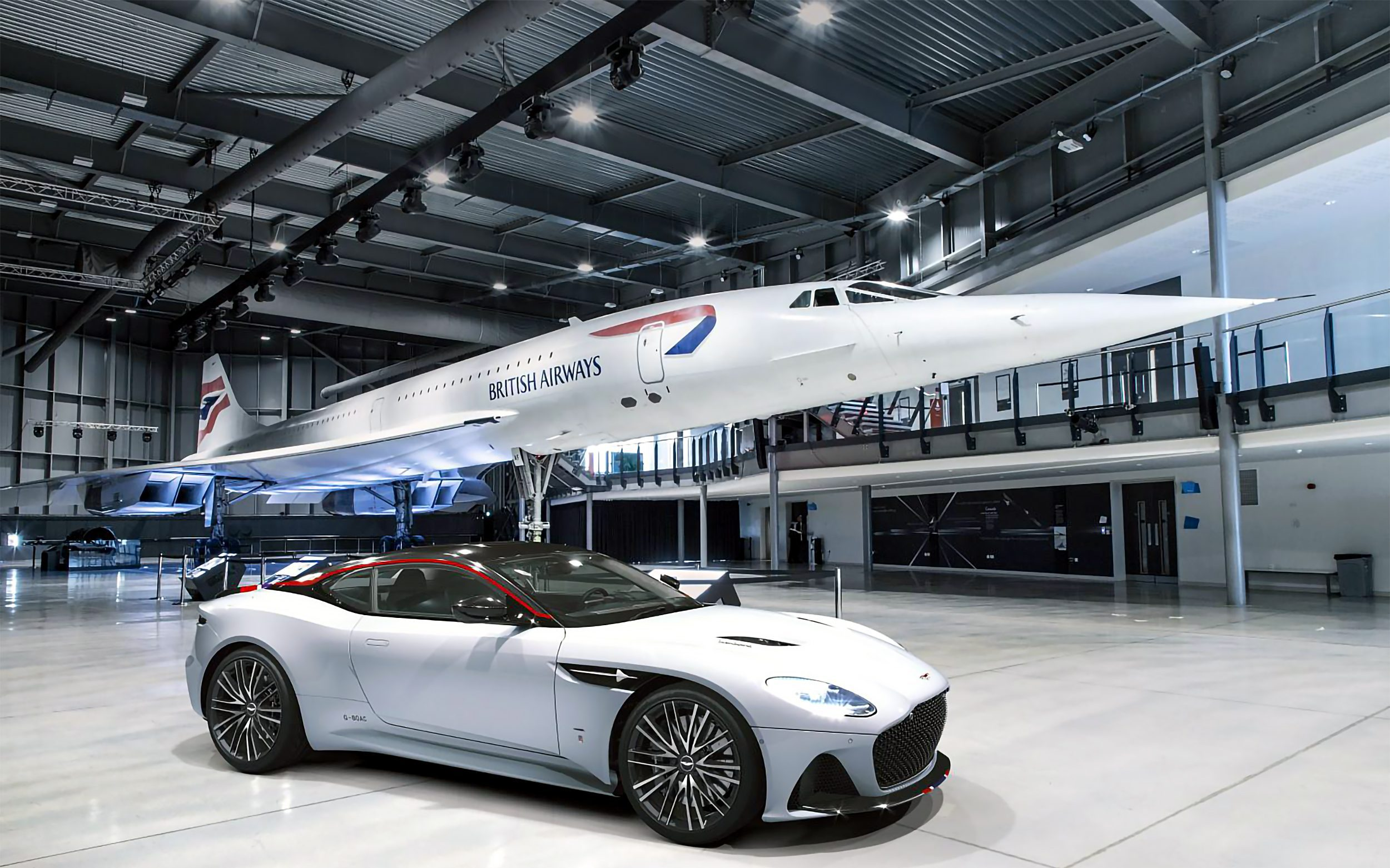 An Aston Martin and a Concorde aeroplane in a hangar with grey Prihoda fabric ducts