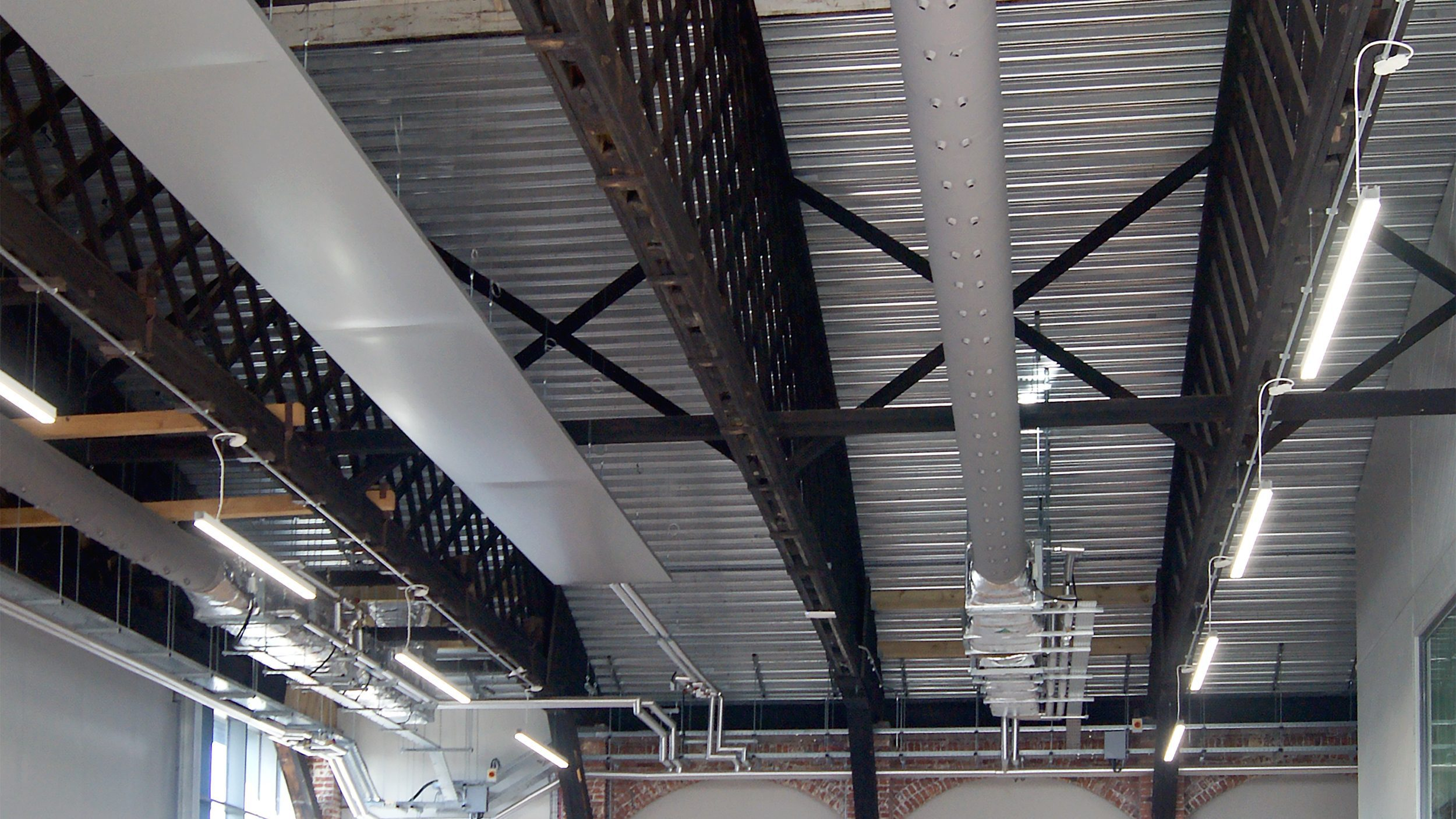 Grey Prihoda textile diffusers with nozzles on the ceiling of a canteen