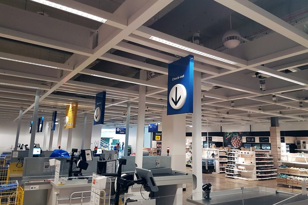 Grey fabric ducts in the ceiling above retail checkout tills